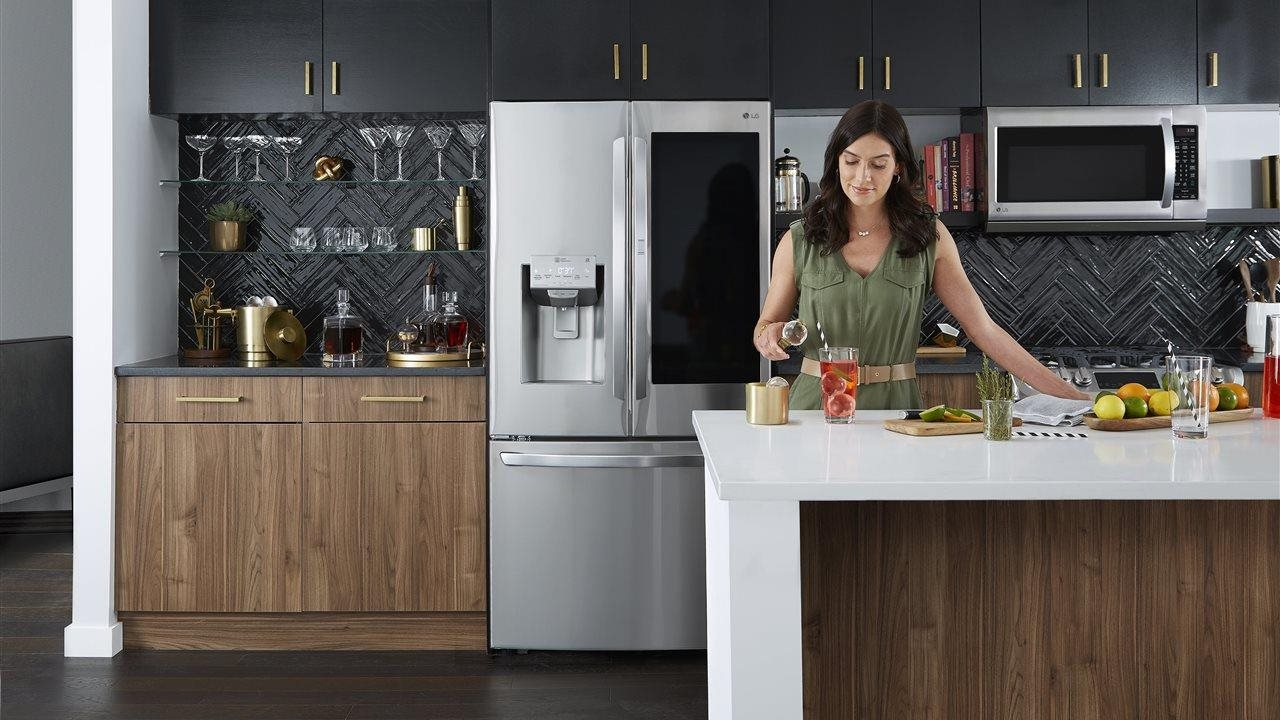 Mom making a beverage in a modern kitchen featuring LG appliances