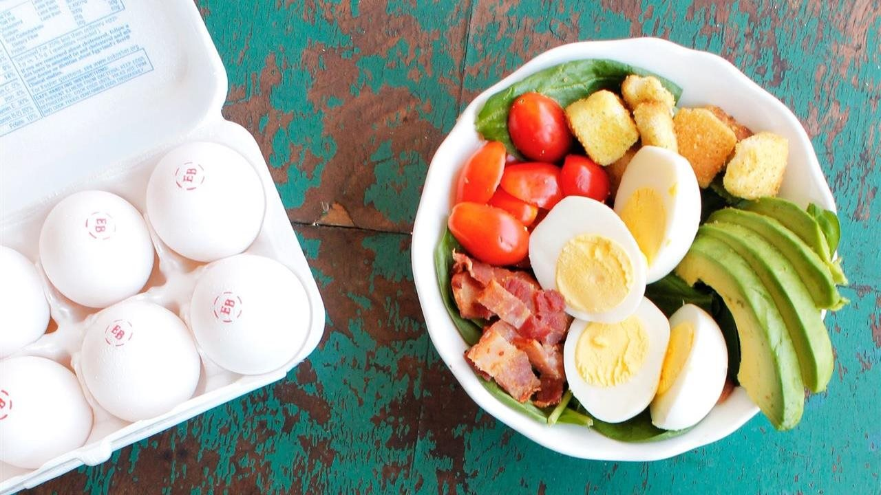 Open egg carton, stamped with EB. Salad with boiled egg in a white bowl sits next to it.