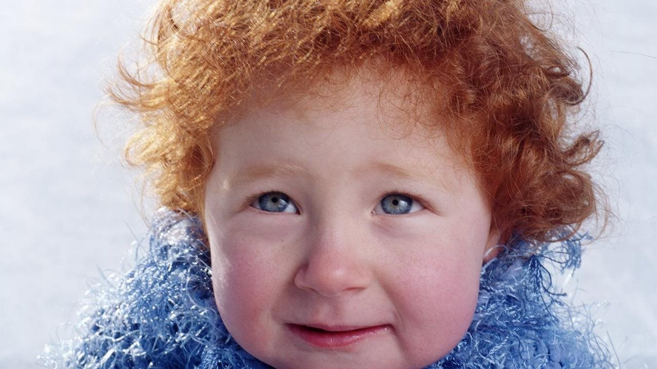 little girl in fuzzy blue sweater with red hair and rosy cheeks