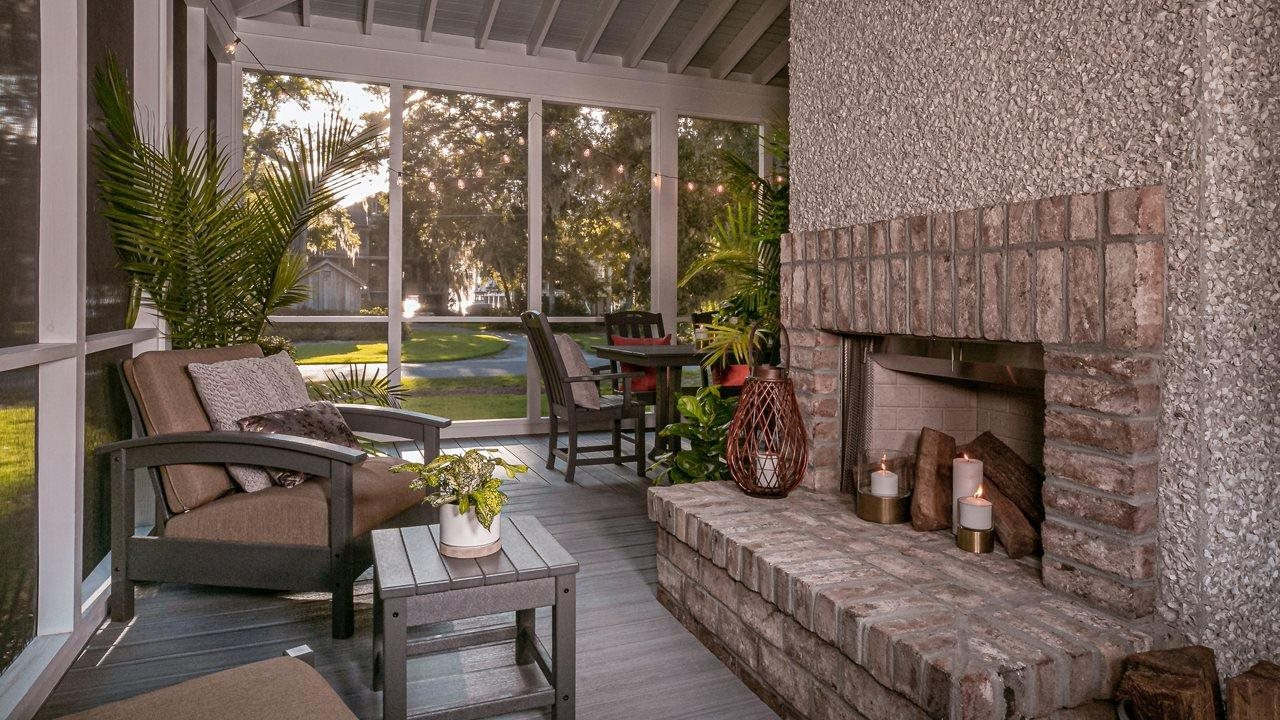 Outdoor screened living area with furniture and fireplace