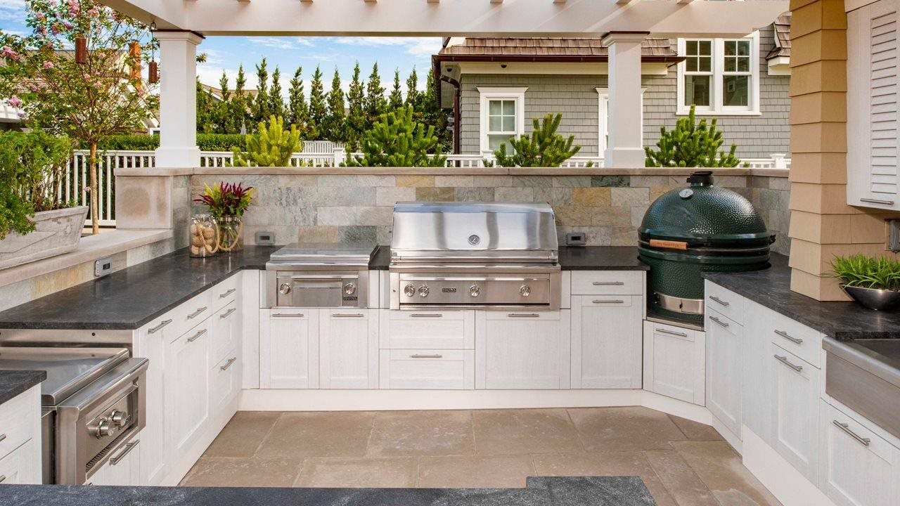 outdoor kitchen with stove oven and grill on tile patio with pergala