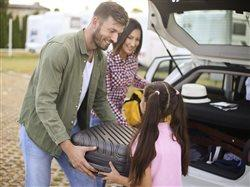 family packing the car for a road trip