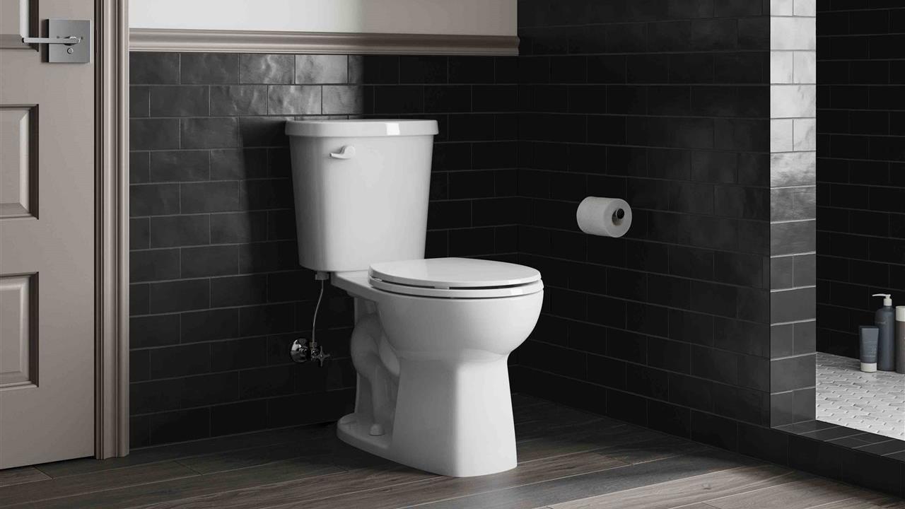 toilet in stylish subway tiled bath