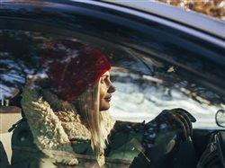 woman dressed for winter driving a car