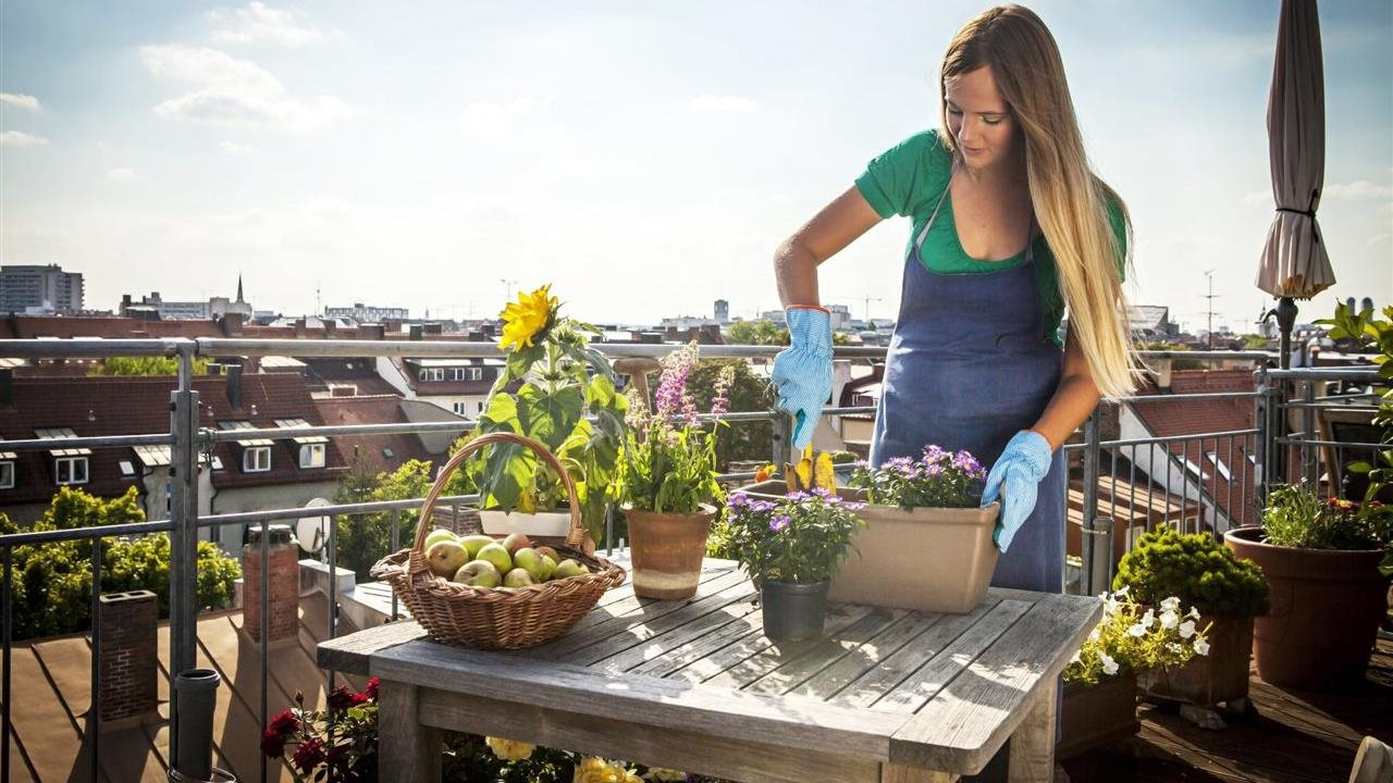 Woman planting flowers and vegetables on her deck
