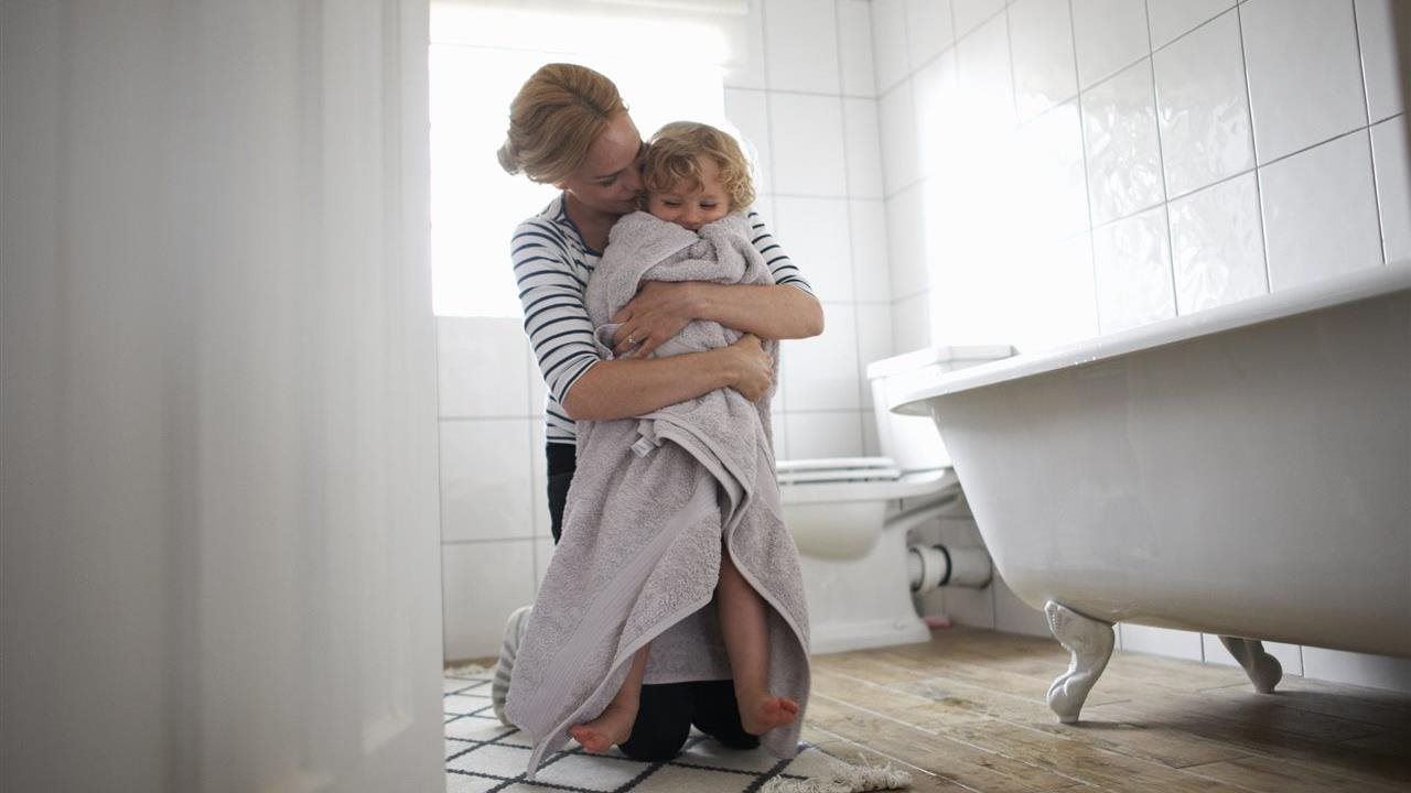 Woman snuggling child in bath towel in bathroom