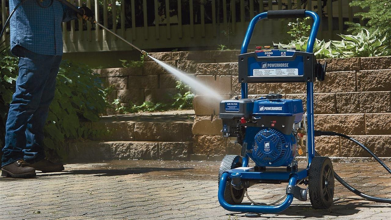 Man using a power washer on stones and drive way