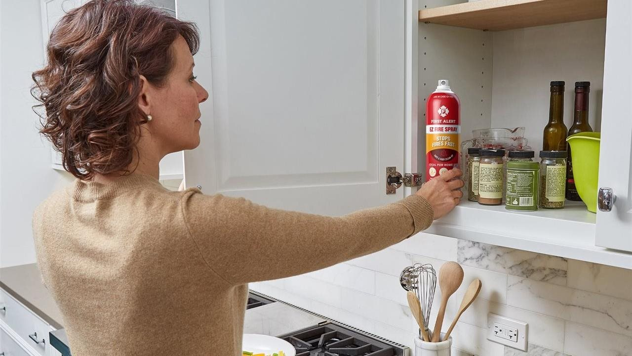 Woman reaching for ez-fire spray in cabinet