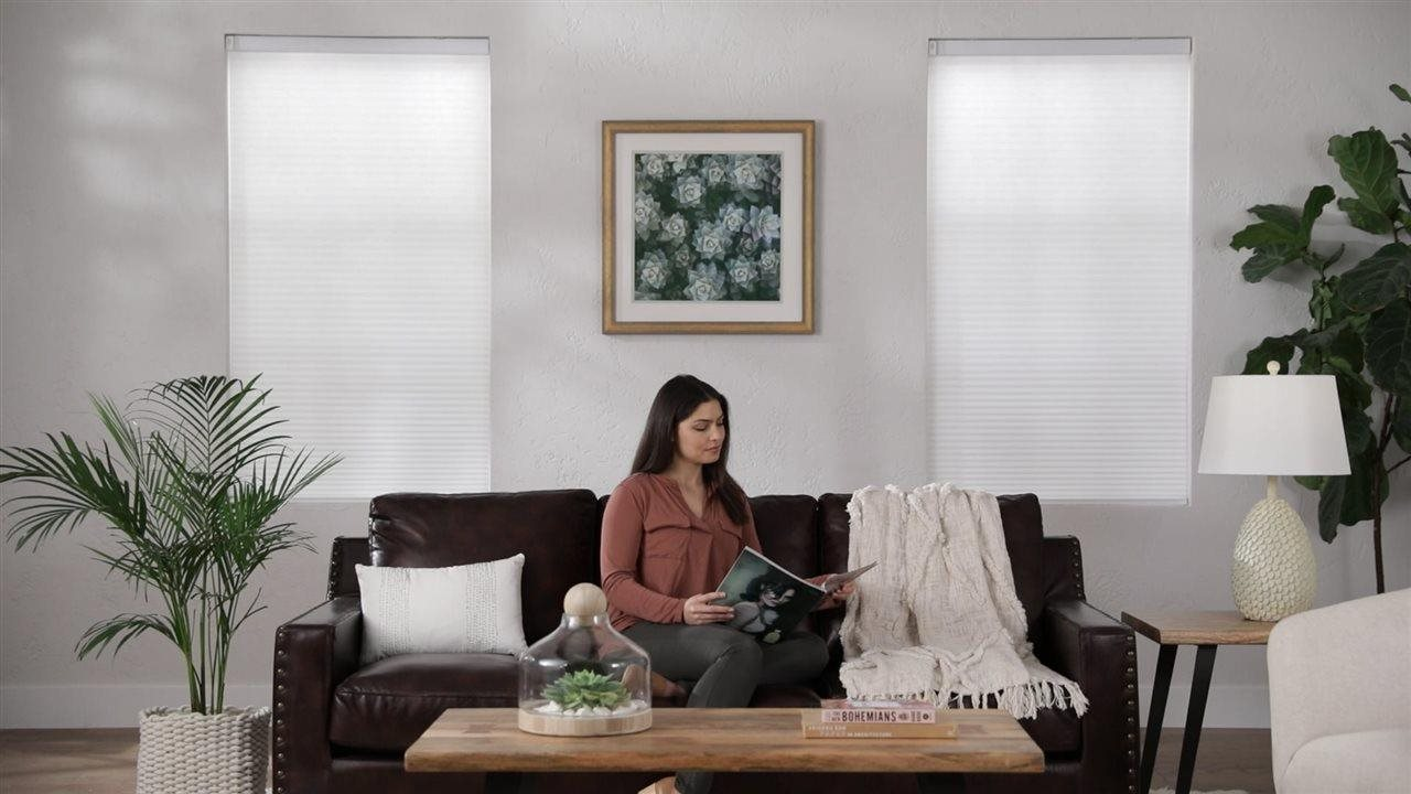 woman sitting on the sofa in the livingroom near window with cellular shades