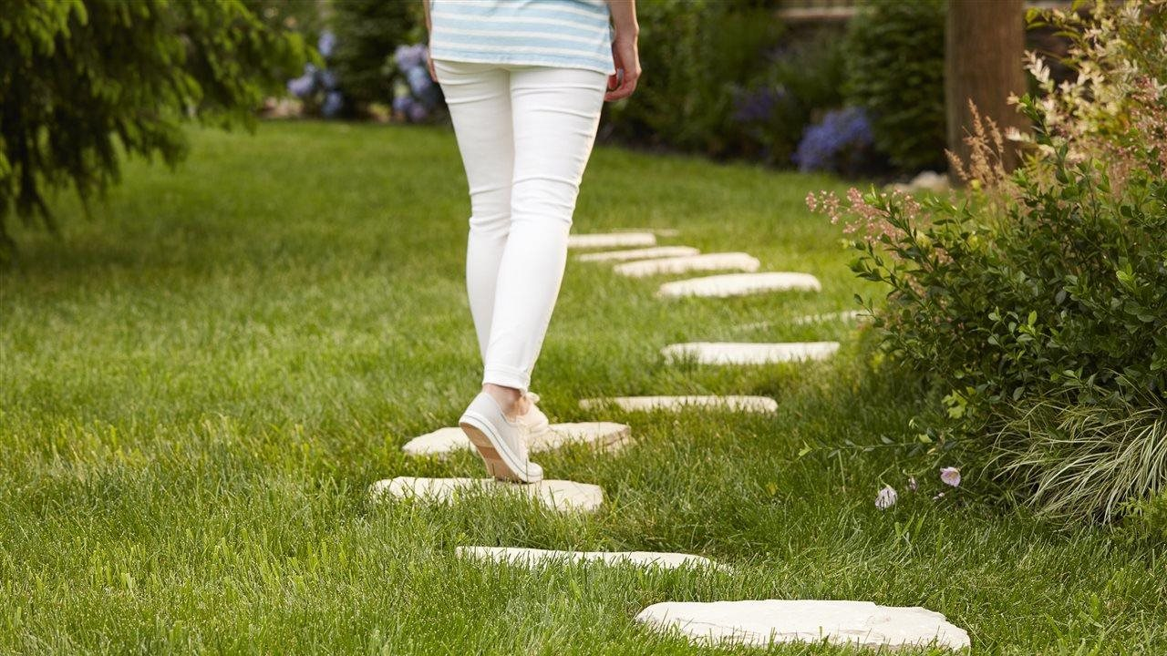 woman walking on pavers through a beautiful lush green lawn