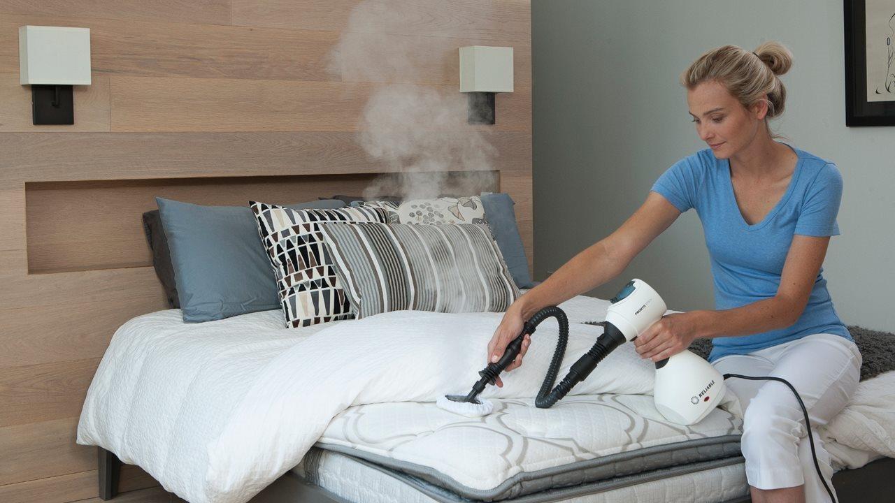 woman steam cleaning a mattress