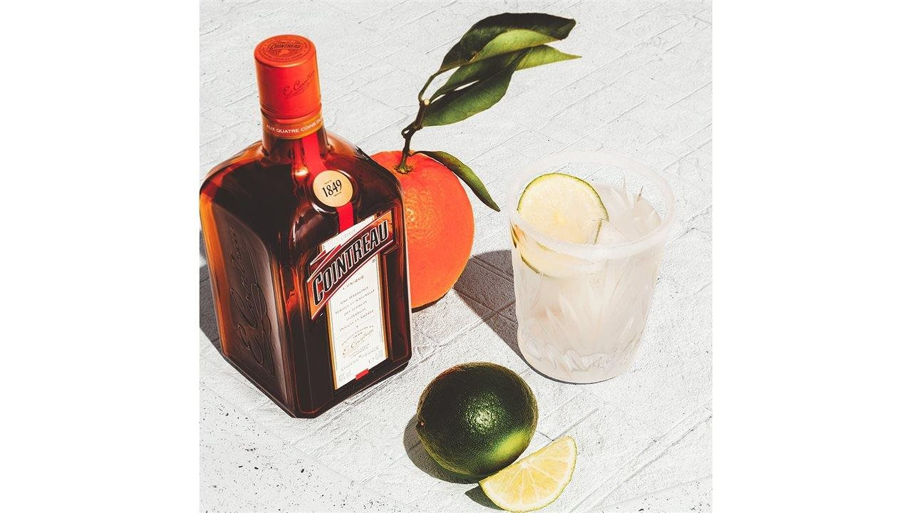bottle of Cointreau near glass, orange and lime