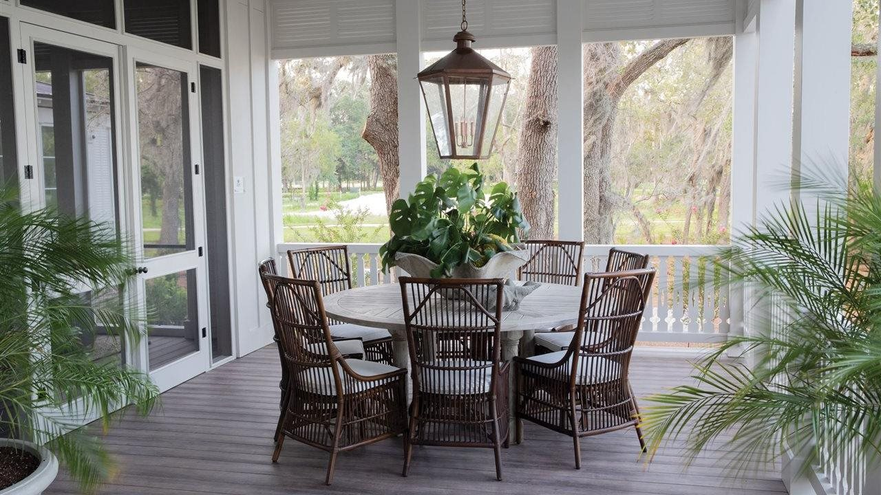 inviting 3 season porch with huge lantern light high ceilings and beautiful table and chairs