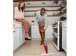 Man cleaning the floor in the kitchen while woman watches