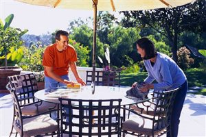 Couple storing their patio furniture