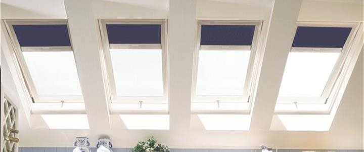 skylights in a kitchen with light blue walls and white cabinets