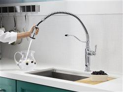 woman using pot filler faucet in sink