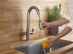 woman using sprayer on American Standard Beale faucet to wash pepper