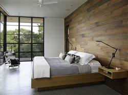 Platform bed with wood wall behind, floor to ceiling corner windows let in day light.