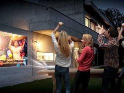 friends watching a beam tv outside