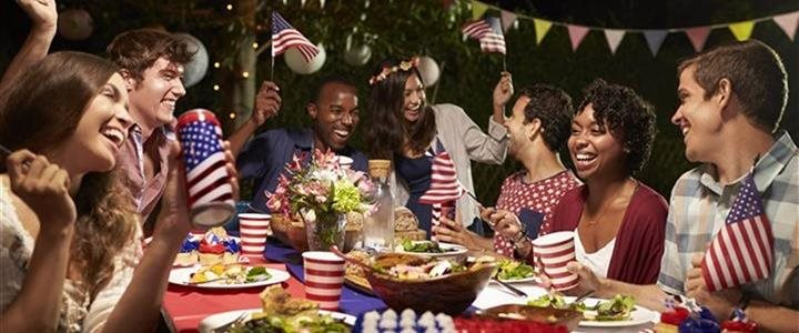 Young adults celebrating Fourth of July picnic in back yard