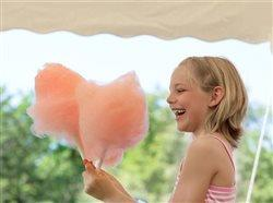 Young girl smiling holding cotton candy outdoors at fair