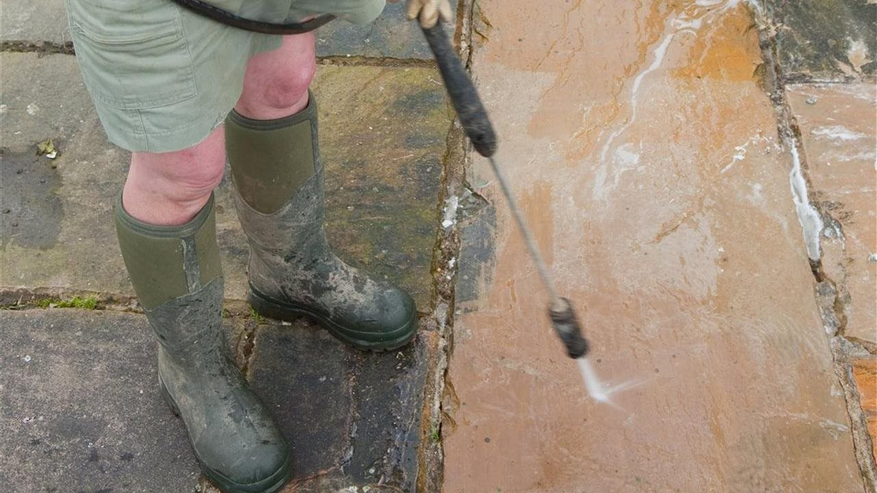 woman power washing stone