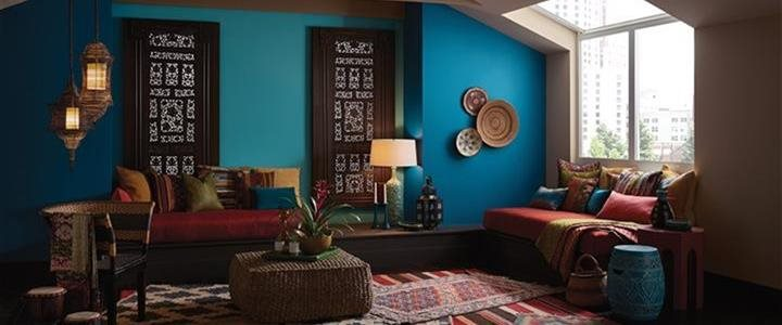 Rich turquoise walls with muted colorful rugs in living room