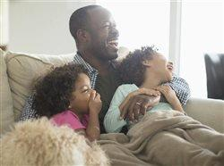 African American father and two young daughters laughing on couch together