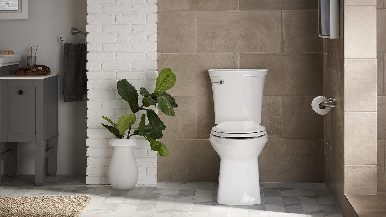 Tiled Bathroom with sleek looking toilet, fiddle-leaf fig in a vase nearby.
