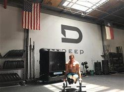man working out in a gym with fan behind him