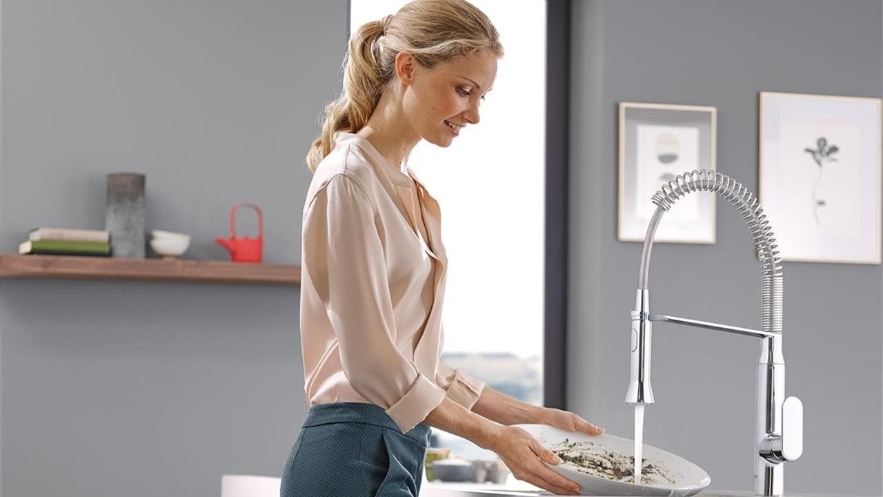 woman rinsing off plate with pull faucet in kitchen sink