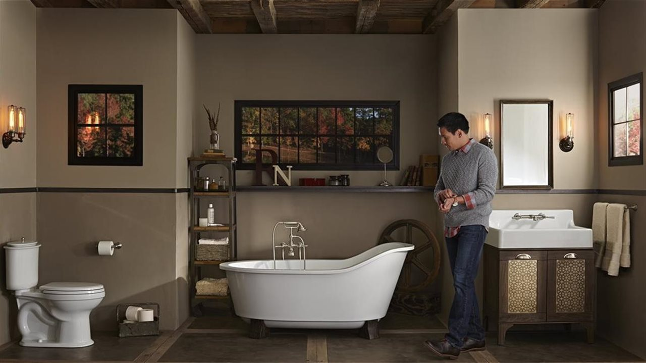 man taking his watch off in a beautiful bath with full tub and matching fixtures