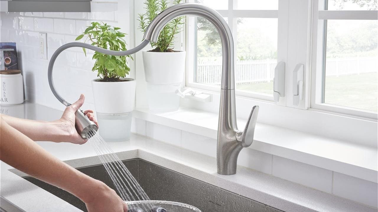 Woman washing items in a bowl in a sink with a spray faucet