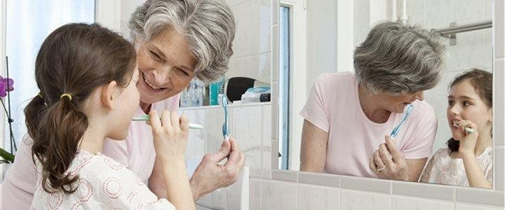 Grandmother and granddaughter brushing sharing a sink in the bathroom.