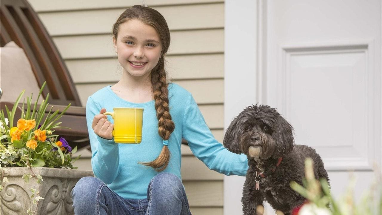 little girl drinking tea on front porch with dog