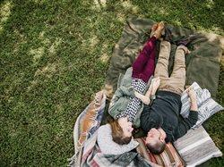 Millennial couple laying on blanket outdoors on grass smiling in fall