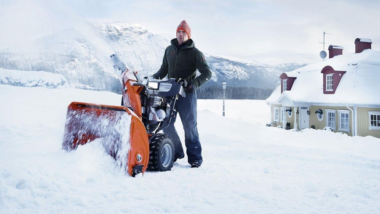 Man outdoors in snow using Husqvarna snow blower