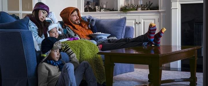 family of four dressed up in winter outdoor clothes watching TV in the their living room