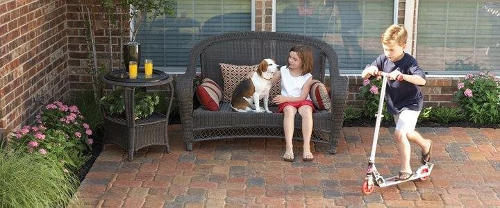 kids and a dog on a paved patio in the backyard