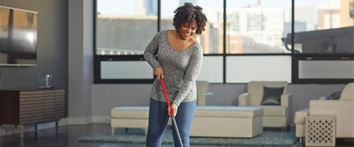 woman mopping floor in living area