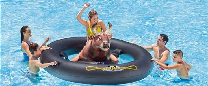 group of friends riding an inflatable bull in a swimming pool