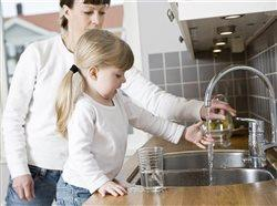 little girl running water in the sink