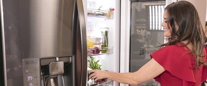 Woman opening LG refridgerator