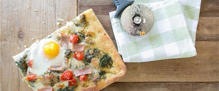 pizza with egg on top and a pizza cutter
