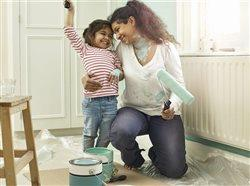 mom and daughter having fun painting a room together