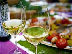 two glasses of white wine in the foreground and food in the background