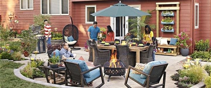 family in backyard oasis with outdoor kitchen, furniture and firepit