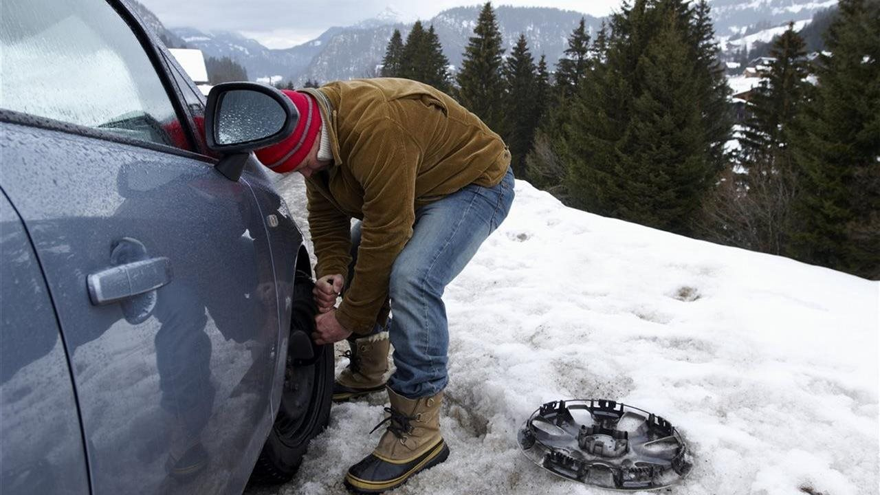 man changing car tire in the snow