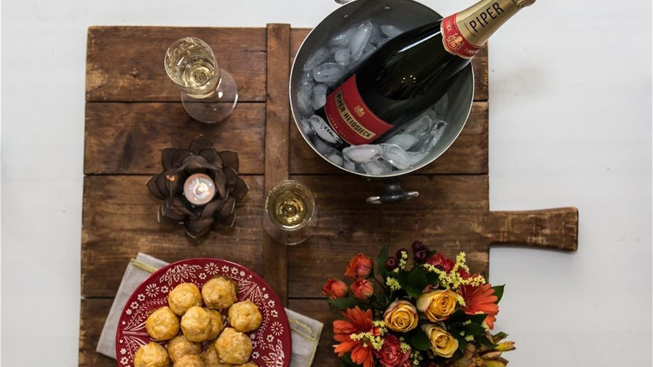 champagne in fluted wine glasses, gougeres and flowers